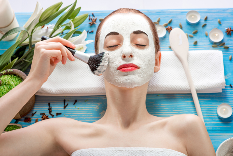 Young woman with spa facial mask on her face lying on blue table with flower, candles and sea salt in the beaty salon